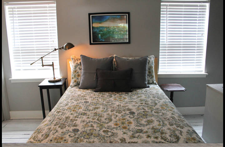 Comfortable queen-sized bed in bedroom that gets natural light during the day.