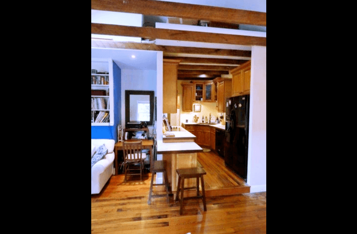 Open living area with hardwood floors, beams, and adjacent kitchen.
