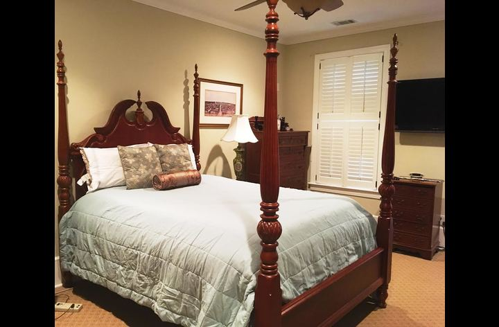 Master bedroom with queen-size bed, balcony, en suite bathroom with jacuzzi tub, and walk-in closet.